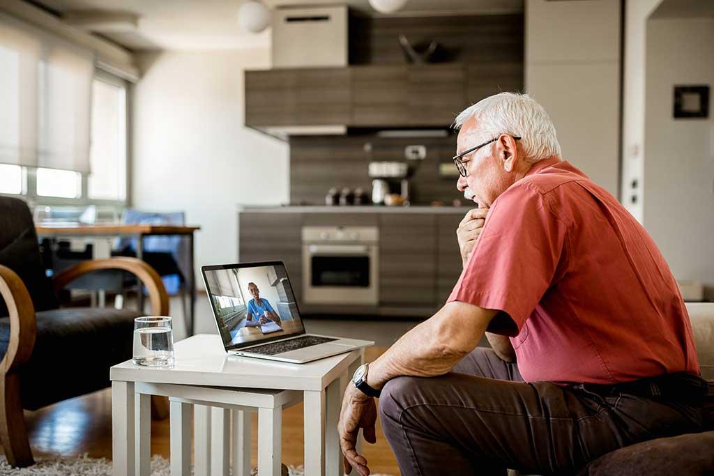 man looking at computer tele health